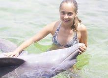 Forma de vida de las vacaciones - adolescente feliz que abraza un delfín Fotografía de archivo libre de regalías