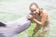 Forma de vida de las vacaciones - adolescente feliz que abraza un delfín Imagen de archivo libre de regalías