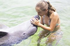 Forma de vida de las vacaciones - adolescente feliz que abraza un delfín Foto de archivo