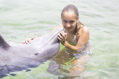 Forma de vida de las vacaciones - adolescente feliz que abraza un delfín Imagenes de archivo