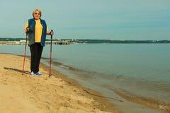 Forma de vida madura activa el caminar nórdico mayor en una playa arenosa Imagenes de archivo