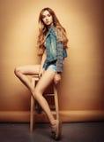 Forma de vida, moda y concepto de la gente: Retrato lleno del cuerpo del modelo de moda que se sienta en la silla de madera en es Fotografía de archivo libre de regalías
