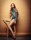 Forma de vida, moda y concepto de la gente: Retrato lleno del cuerpo del modelo de moda que se sienta en la silla de madera en es Fotos de archivo