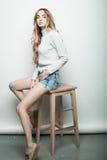 Forma de vida, moda y concepto de la gente: Retrato lleno del cuerpo del modelo de moda que se sienta en la silla de madera en es Fotografía de archivo