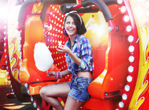 Forma de vida. Mujer feliz joven que come el caramelo de algodón azucarado en Funfair Foto de archivo