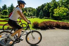 Forma de vida sana - bicicletas que montan de la gente en parque de la ciudad Imagen de archivo libre de regalías