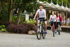 Forma de vida sana - bicicletas que montan de la gente en parque de la ciudad Fotos de archivo libres de regalías