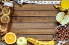 Forma de vida sana; botella de la aptitud; dan fruto las naranjas; manzanas y plátanos; avellanas y cacahuetes; zumo y cinta métr imagen de archivo libre de regalías