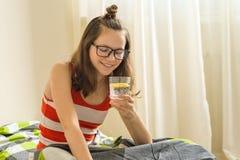 Forma de vida sana, dieta, antioxidante Vidrio de la mañana de agua con el limón en las manos del adolescente Fotos de archivo libres de regalías