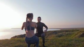 Forma de vida sana, mujer atlética de los pares y hombre llevando a cabo las manos y agachándose simultáneamente en luz del sol e almacen de metraje de vídeo