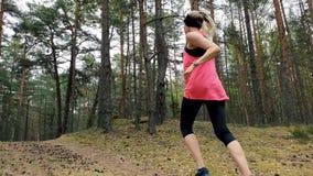 Forma de vida sana - mujer que activa en rastro del bosque almacen de metraje de vídeo