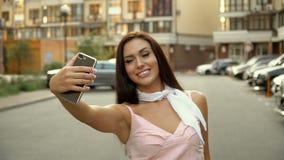 Forma de vida de Selfie Retrato de una mujer positiva joven que se divierte y que toma un selfie en el centro de ciudad metrajes