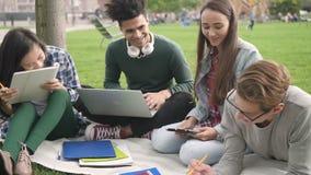 Forma de vida tirada de hablar de cuatro personas americano usando el ordenador a lo largo de la universidad metrajes