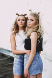 Forma de vida y concepto de la gente: Retrato de la moda de dos mejores amigos elegantes de las muchachas que llevan las faldas d Imagen de archivo libre de regalías