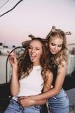 Forma de vida y concepto de la gente: Retrato de la moda de dos mejores amigos elegantes de las muchachas que llevan las faldas d Fotografía de archivo libre de regalías