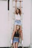 Forma de vida y concepto de la gente: Retrato de la moda de dos mejores amigos elegantes de las muchachas que llevan las faldas d Imágenes de archivo libres de regalías