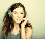 Forma de vida y concepto de la gente: la mujer joven con los auriculares escucha Fotografía de archivo