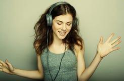 Forma de vida y concepto de la gente: la mujer joven con los auriculares escucha Fotos de archivo libres de regalías