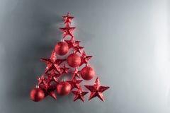 Forma del árbol de navidad con las estrellas y las chucherías del rojo Imagen de archivo