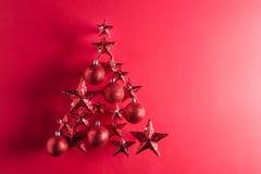 Forma del árbol de navidad con las estrellas y las chucherías del rojo Fotografía de archivo