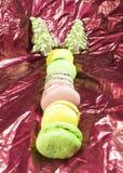 Forma del árbol del Año Nuevo de las galletas del jengibre y galletas de los macarrones en fondo rojo Fotos de archivo libres de regalías
