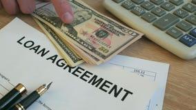 Forma del acuerdo de préstamo Hombre que pone el dinero en un escritorio metrajes