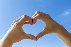 Forma del corazón con la mano debajo del cielo azul Imagen de archivo
