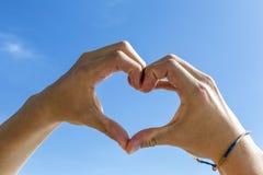 Forma del corazón con la mano debajo del cielo azul Fotografía de archivo libre de regalías