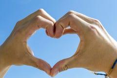 Forma del corazón con la mano debajo del cielo azul Fotos de archivo libres de regalías