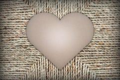 Forma del corazón de la cartulina en fondo de la cesta de mimbre Espacio para el texto fotografía de archivo