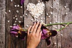 Forma del corazón de las flores y de la mano blancas de la lila con el anillo en la madera TA Imagen de archivo libre de regalías
