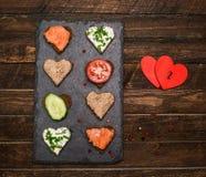 Forma del corazón de los Canapes con diversos desmoches en tablero negro de la pizarra Foto de archivo
