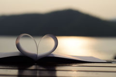 Forma del corazón del libro de papel en la puesta del sol con el reflejo de luz en una superficie del agua (fondo del vintage) Imagen de archivo libre de regalías