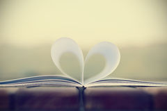 Forma del corazón del libro de papel en la tabla de madera (fondo del vintage) Fotografía de archivo