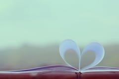 Forma del corazón del libro de papel en la tabla de madera (fondo del vintage) Fotografía de archivo libre de regalías