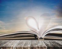 Forma del corazón en la página abierta del cuaderno, en la tabla de madera, con el cielo de la puesta del sol en fondo del verano Foto de archivo libre de regalías