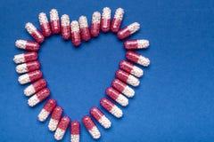 Forma del corazón del fondo médico de las píldoras un fondo encima azul imagen de archivo