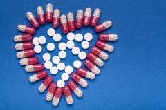 Forma del corazón del fondo médico de las píldoras un fondo encima azul imagen de archivo libre de regalías
