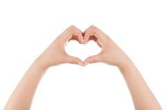 Forma del corazón hecha de las dos manos de la mujer. Foto de archivo