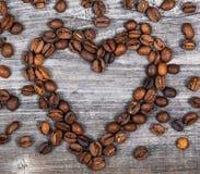 Forma del corazón hecha de los granos de café en fondo de madera Fotografía de archivo
