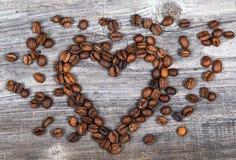 Forma del corazón hecha de los granos de café en fondo de madera Imagen de archivo libre de regalías