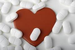 Forma del corazón rodeada por las píldoras Foto de archivo