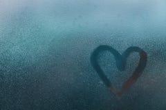 Forma del corazón sobre el vidrio con descensos del agua Foto de archivo libre de regalías