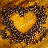 Forma del corazón hecha de los granos de café en superficie de madera Imagen de archivo libre de regalías