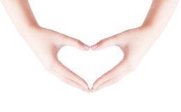 Forma del cuore che fa delle mani fotografia stock