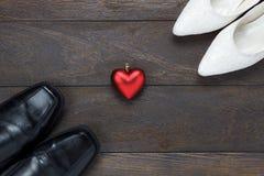 Forma del cuore con le scarpe del ` s delle scarpe e delle donne del ` s degli uomini su legno Fotografie Stock Libere da Diritti
