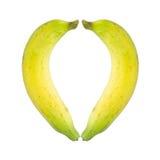 Forma del cuore da una banana di due fette isolata su fondo bianco Fotografia Stock