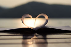 Forma del cuore dal tascabile al tramonto con la riflessione leggera su una superficie dell'acqua (fondo d'annata) Immagini Stock