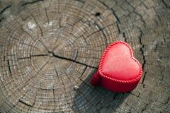 Forma del cuore del contenitore di regalo sul tronco di legno Immagini Stock