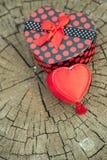 Forma del cuore del contenitore di regalo sul tronco di legno Immagine Stock